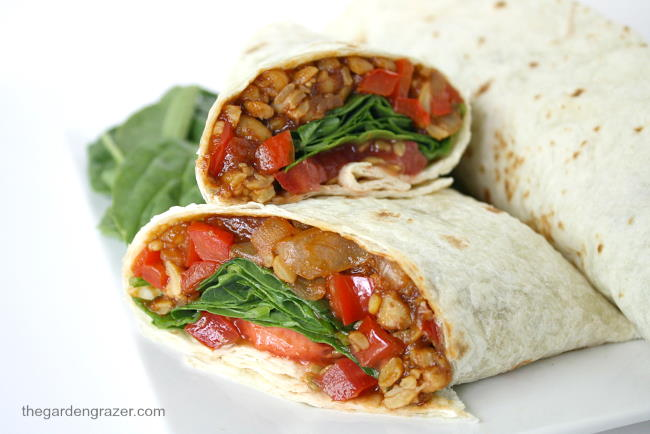 Plate with vegan BBQ tempeh wraps with tomato and spinach