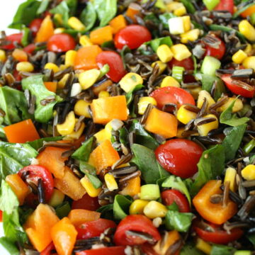 Vegan wild rice salad with spinach and vegetables on a white plate