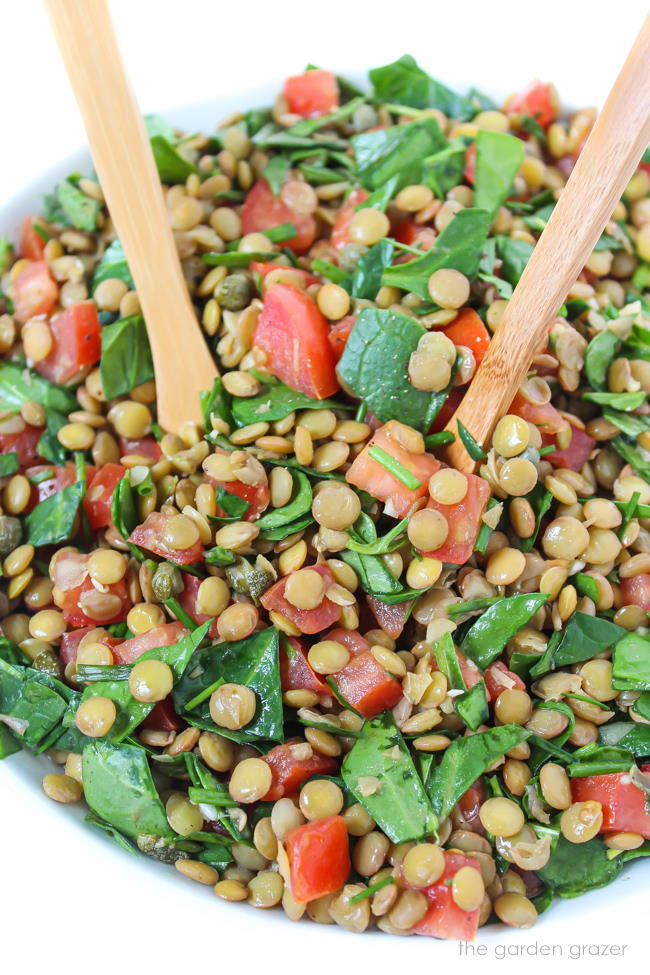 Vegan lentil salad with spinach, tomatoes, and capers