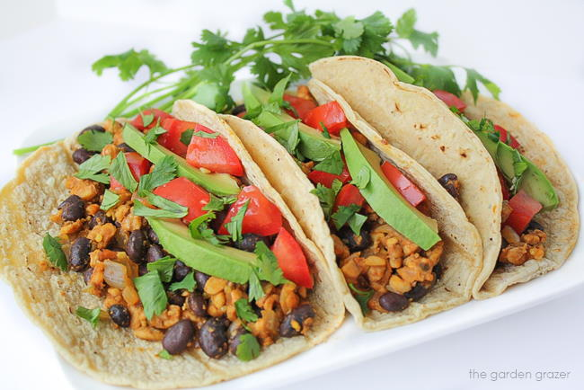 Vegan tempeh and black bean tacos on a white plate