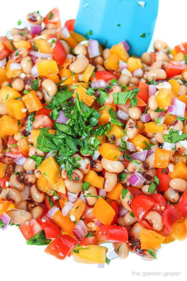 Black Eyed Pea salad being mixed together in a bowl