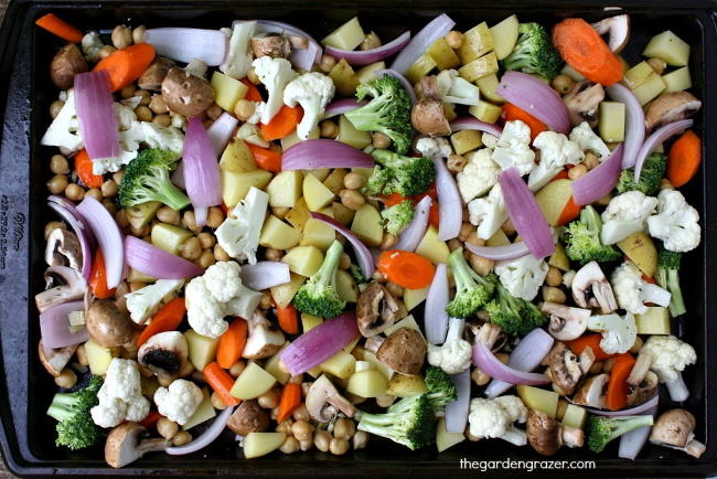 Sheet pan preparation of assorted raw vegetables waiting to be roasted