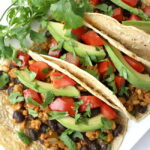 Vegan black bean tempeh tacos on a plate with cilantro garnish
