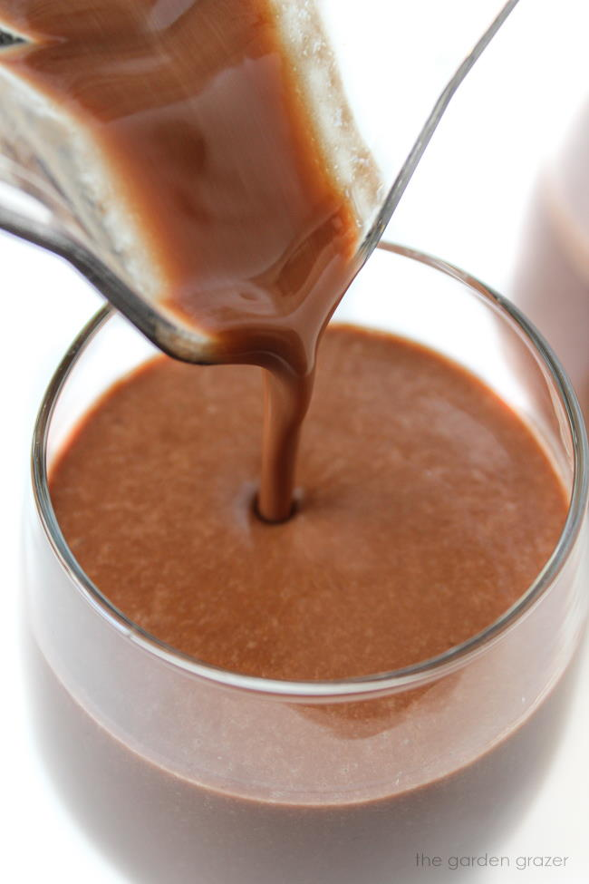 Pouring healthy chocolate milkshake into a glass