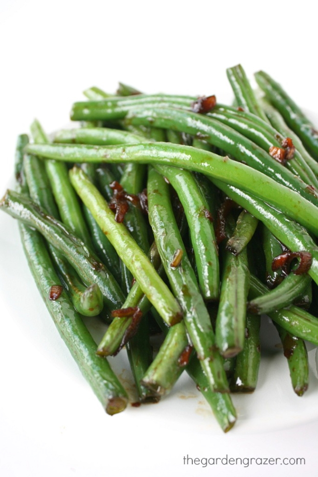 Asian-style garlic green beans on a white plate
