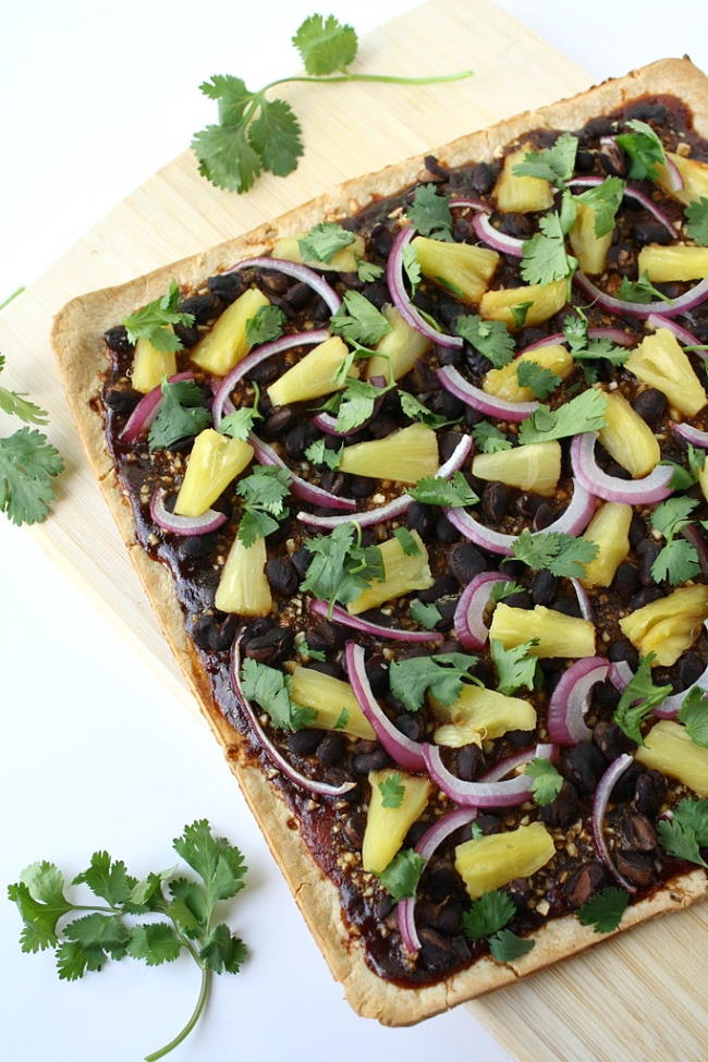 Vegan BBQ pizza with pineapple and black beans cut on a cutting board