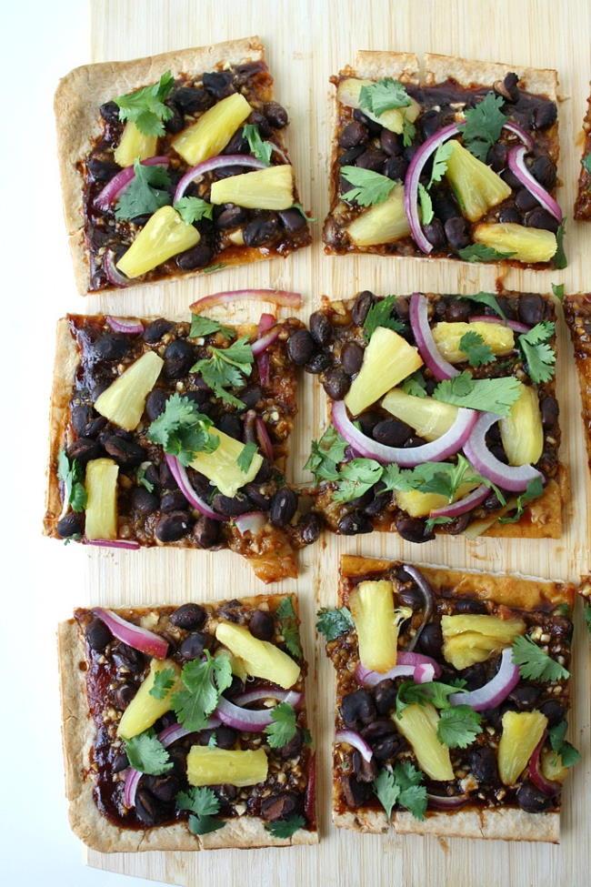 Vegan Hawaiian BBQ pizza with black beans on a cutting board