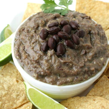 Vegan black bean avocado dip in a bowl with chips on the side