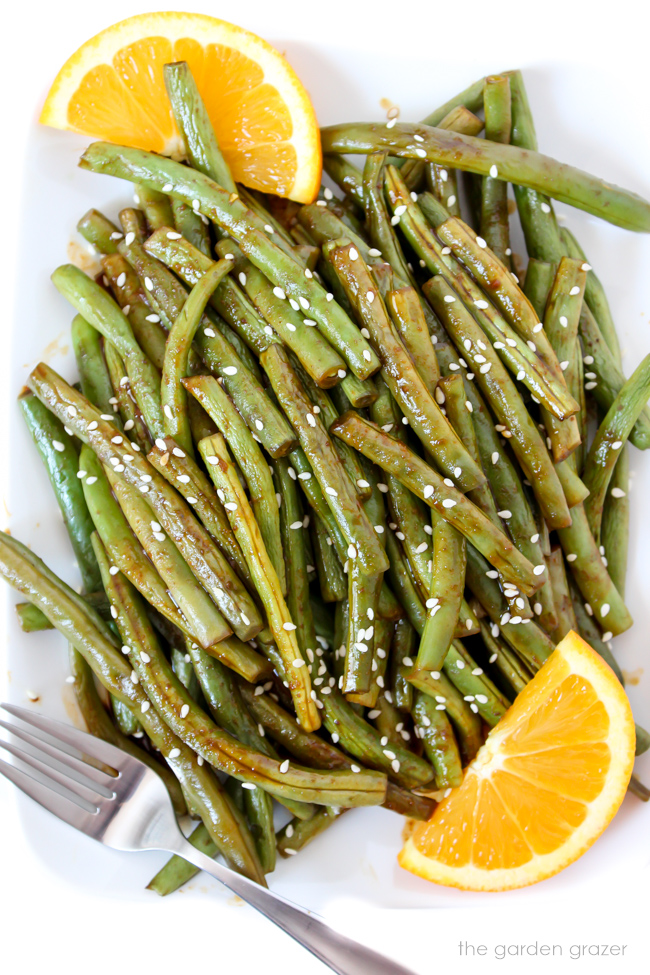 Hoisin green beans on a plate with oranges