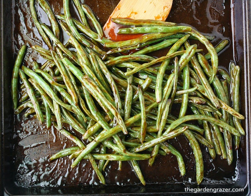 Hoisin roasted green beans on a sheet pan with wooden spatula