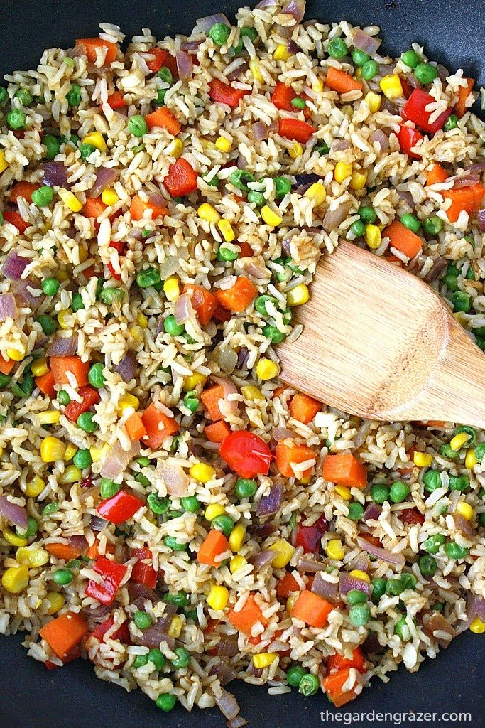 Skillet with vegetable fried rice with wooden spoon