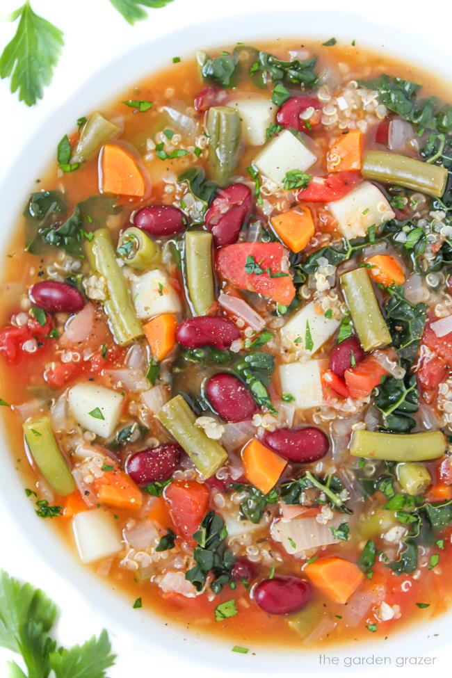 Vegan quinoa minestrone soup with kidney beans in a white bowl