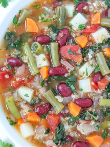 Bowl of vegan quinoa minestrone soup with potato and vegetables