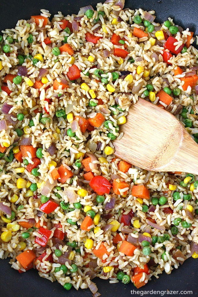 Cooking vegetable fried rice in a skillet with wooden spoon