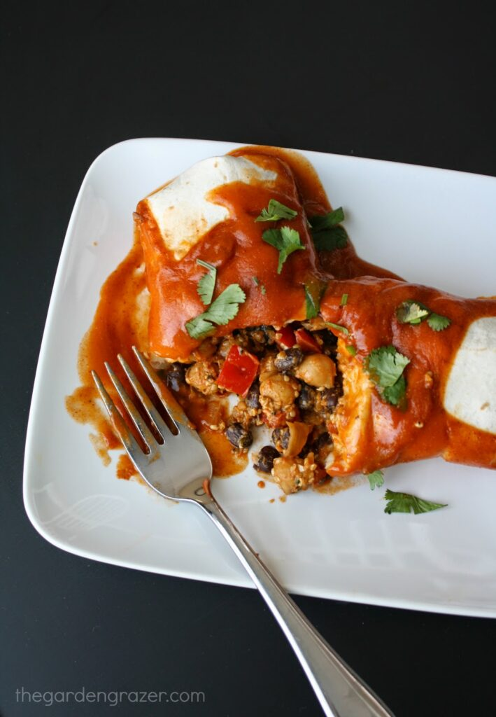 Vegan enchiladas with garbanzos and black beans on a plate with fork