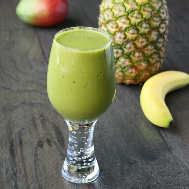 Glass of vegan tropical matcha smoothie with mango and pineapple