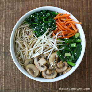 noodle soup in a bowl with bean sprouts, carrots, and mushroom