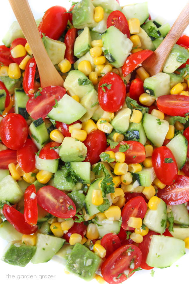 Bowl of vegan avocado summer salad with cucumber, tomato, corn, and herbs