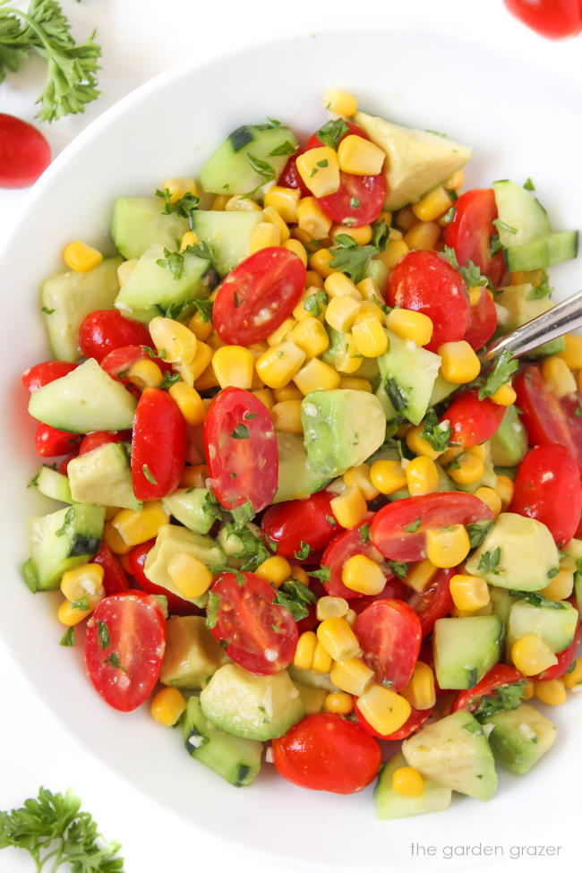 Summer avocado salad with tomato, cucumber, and corn in a bowl with spoon