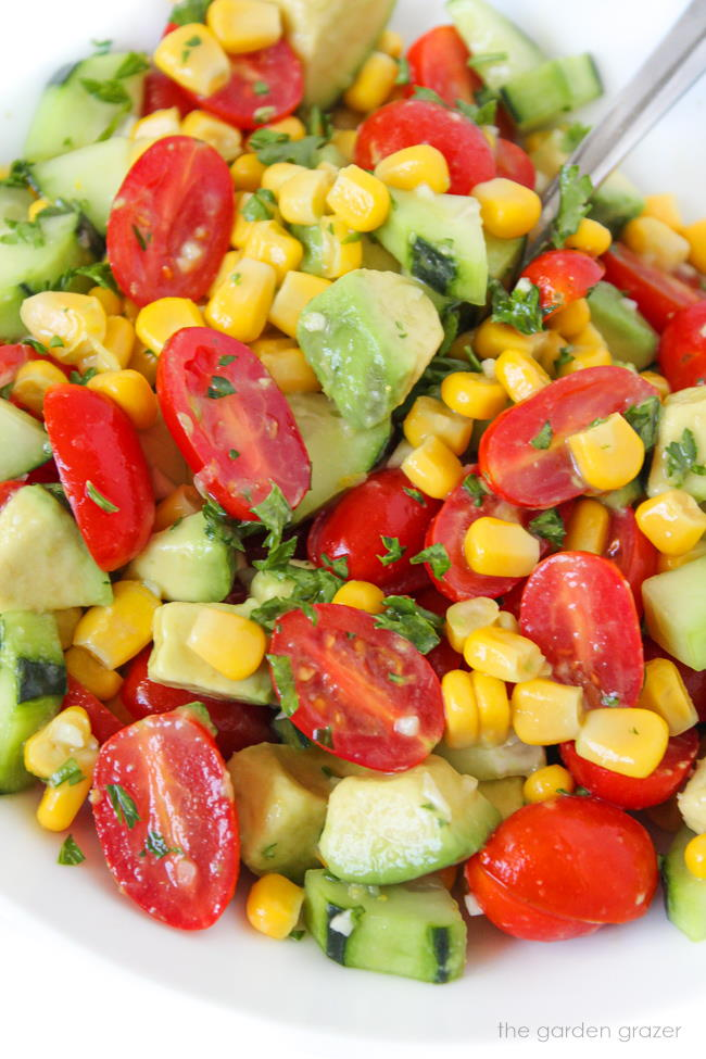 Summer blast salad in a bowl with avocado, tomato, cucumber, and parsley