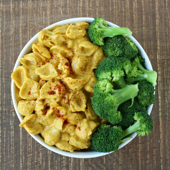 Vegan mac and cheese in a white bowl with broccoli