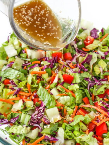 Asian Chopped Salad with sesame dressing being poured on top