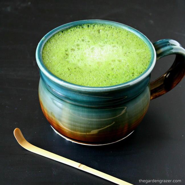 Large mug of vanilla soy matcha latte with bamboo scoop