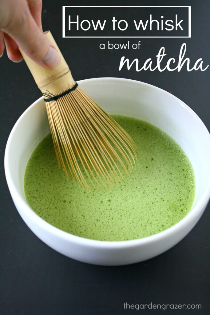 Bowl of matcha green tea with a bamboo whisk