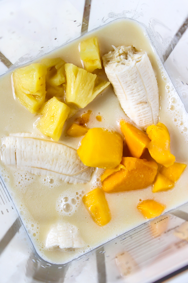 ingredients in a blender for creamy tropical smoothie