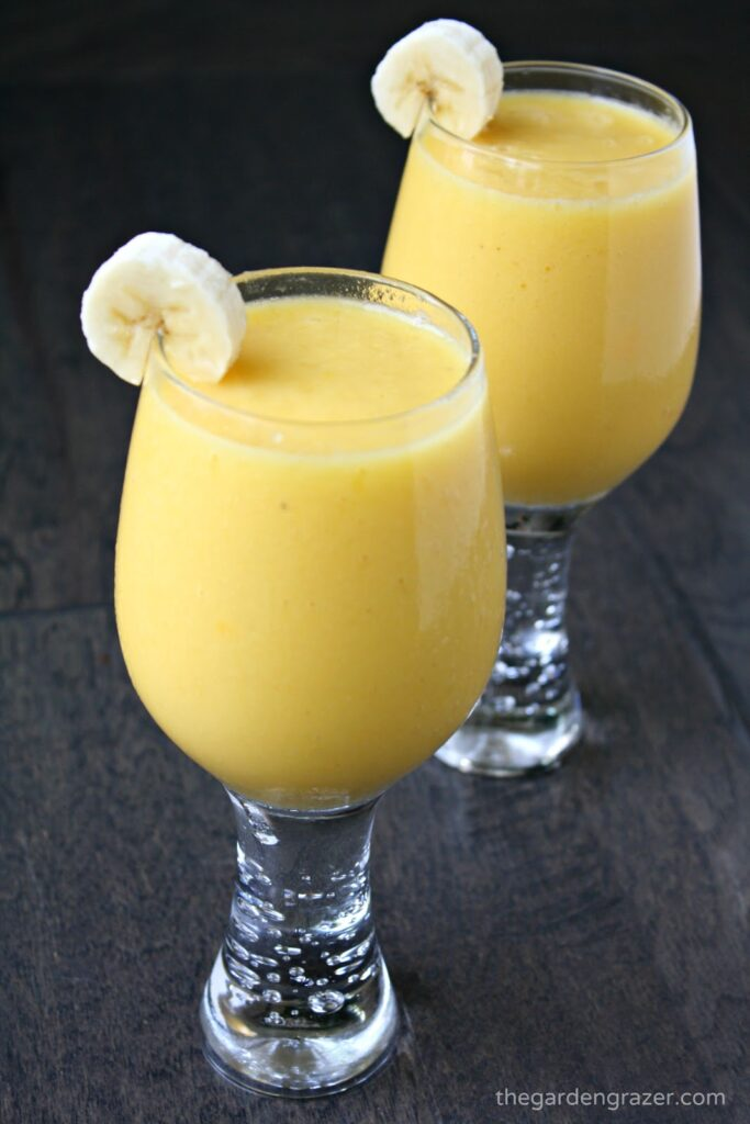 Two glasses with tropical smoothies  and banana garnish