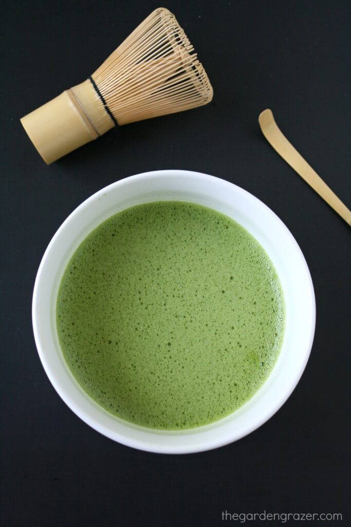 Bowl of whisked matcha green tea with bamboo whisk and scoop