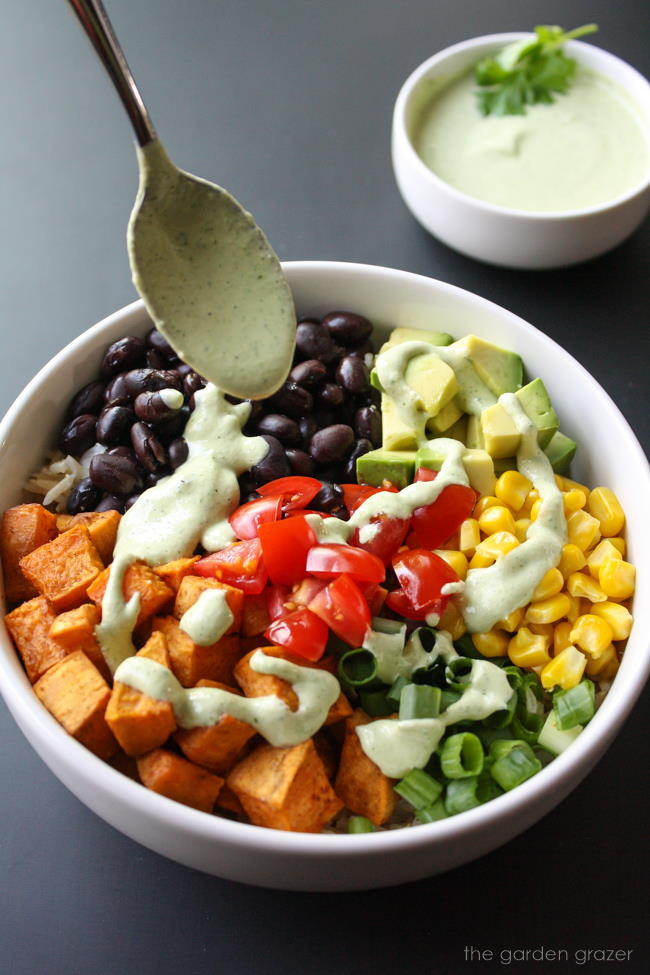 Cashew cream being drizzled over a black bean potato bowl with corn