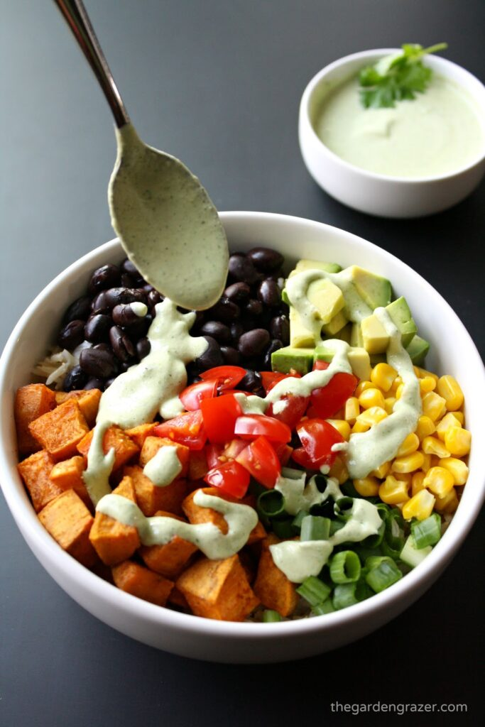 Vegan Mexican sweet potato bowl with dressing being spooned on top