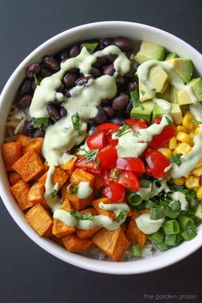 Vegan sweet potato bowl with black beans and cashew cream in a white bowl