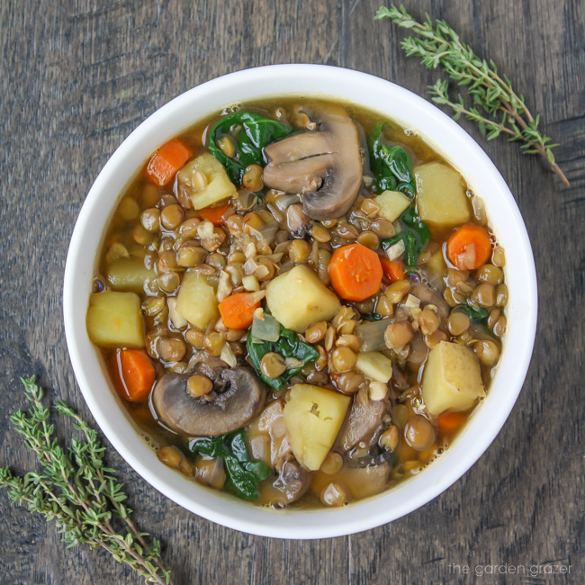Bowl of vegan lentil potato soup garnished with thyme