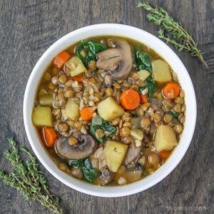 Bowl of vegan lentil potato soup garnished with thyme