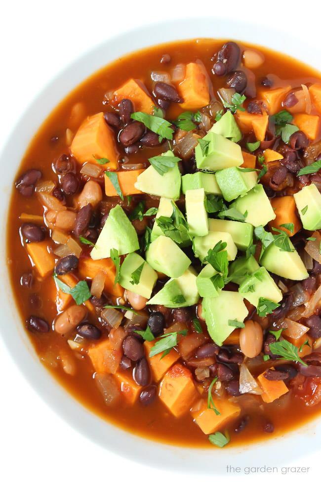 Bowl of vegan sweet potato black bean chili topped with avocado