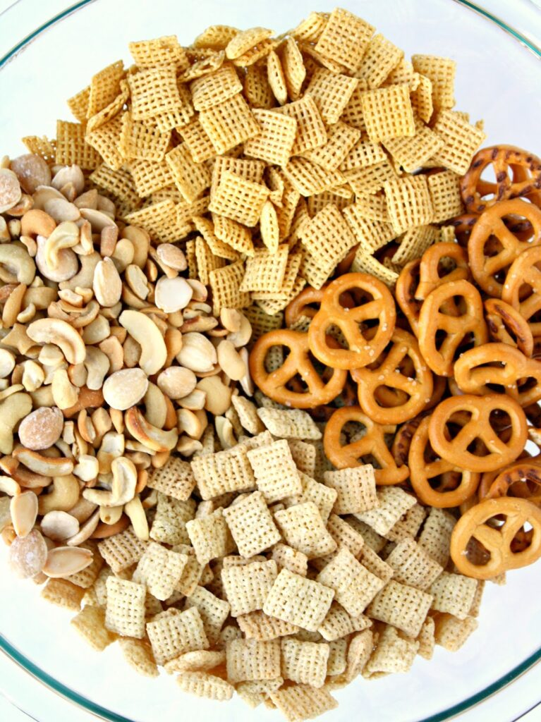 Ingredients for vegan chex mix in a bowl ready to be mixed