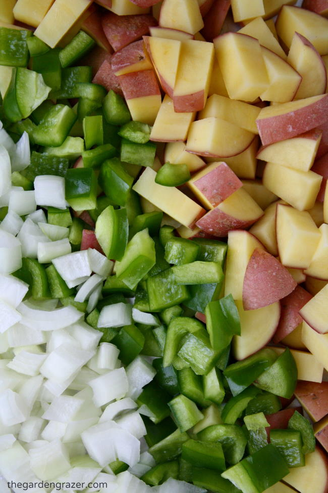 Raw ingredients diced on a cutting board for breakfast potatoes