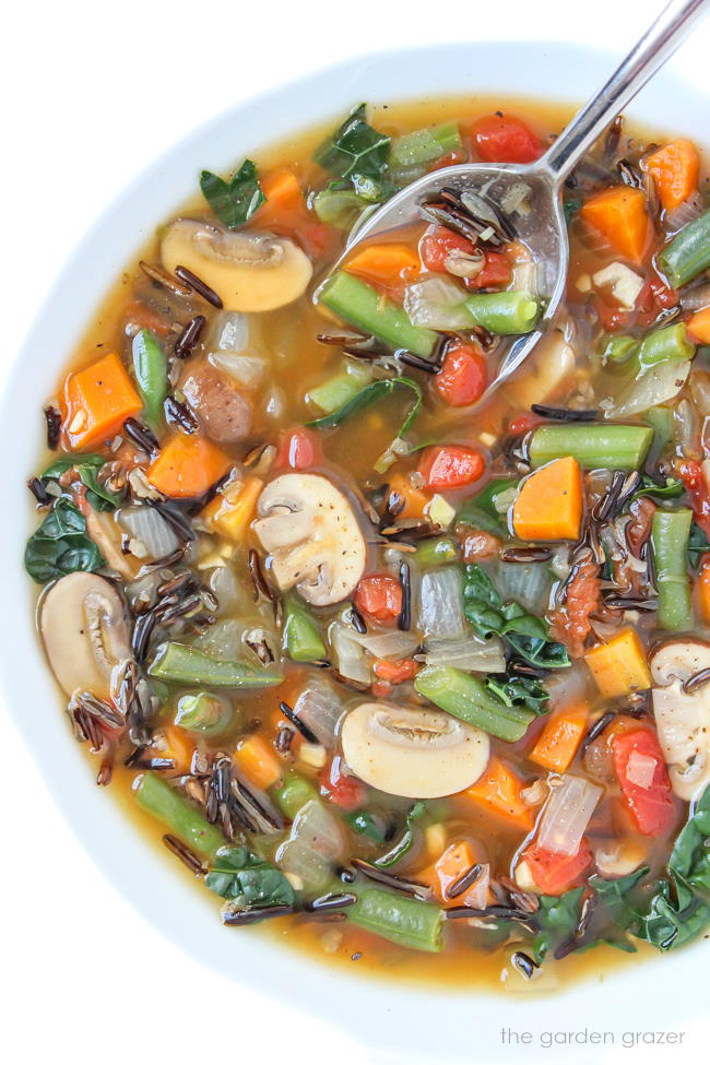 Vegan wild rice vegetable soup in a bowl with spoon