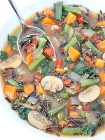 Wild rice vegetable soup in a white bowl with spoon