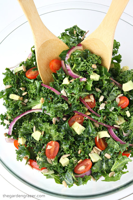 Marinated kale salad in a bowl with bamboo serving utensils