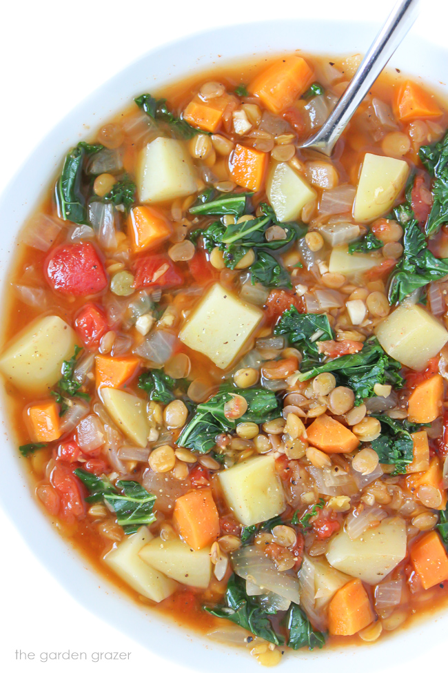 Bowl of vegan lentil kale potato soup with spoon