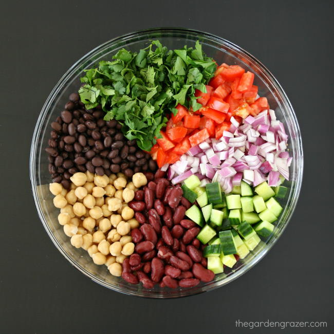 Ingredients for three bean salad in a glass bowl before mixing