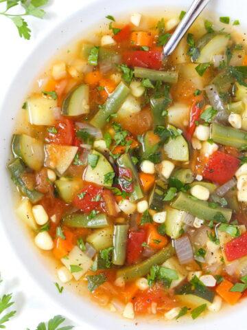 Bowl of vegan garden vegetable soup with fresh herbs