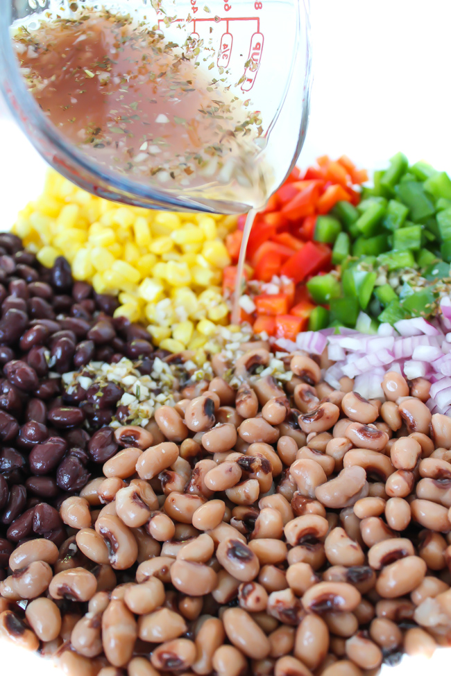 Ingredients for Texas Caviar in a bowl with dressing being poured on top