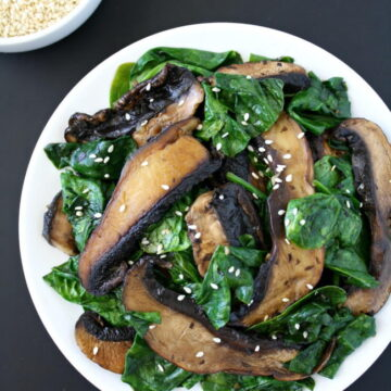 Portobello with spinach topped with sesame seeds on a plate