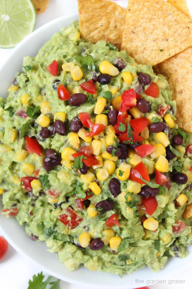 Bowl of black bean fiesta guacamole with cilantro and tomato