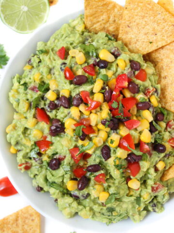 Black bean corn guacamole in a bowl with chips on the side