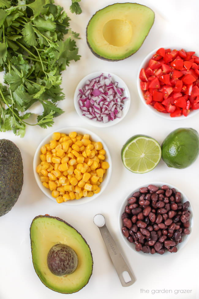 Ingredients on a white table for corn guacamole